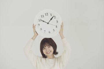 時計を持って微笑む女性